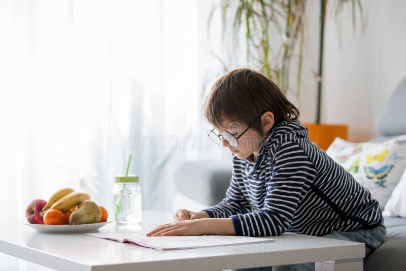 Preschool dziecko z szkłami, pisze pracie domowej w domu obraz stock