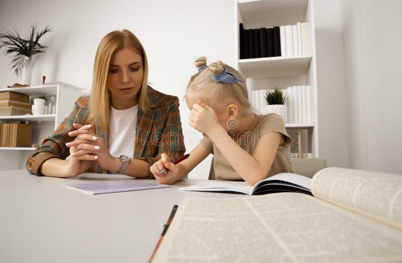 Preschool dziewczyna pisze zadaniu z jej matką przy biurkiem obraz royalty free