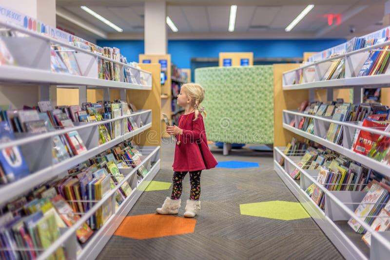 Preschool dziewczyna wybiera książki przy biblioteką obrazy stock