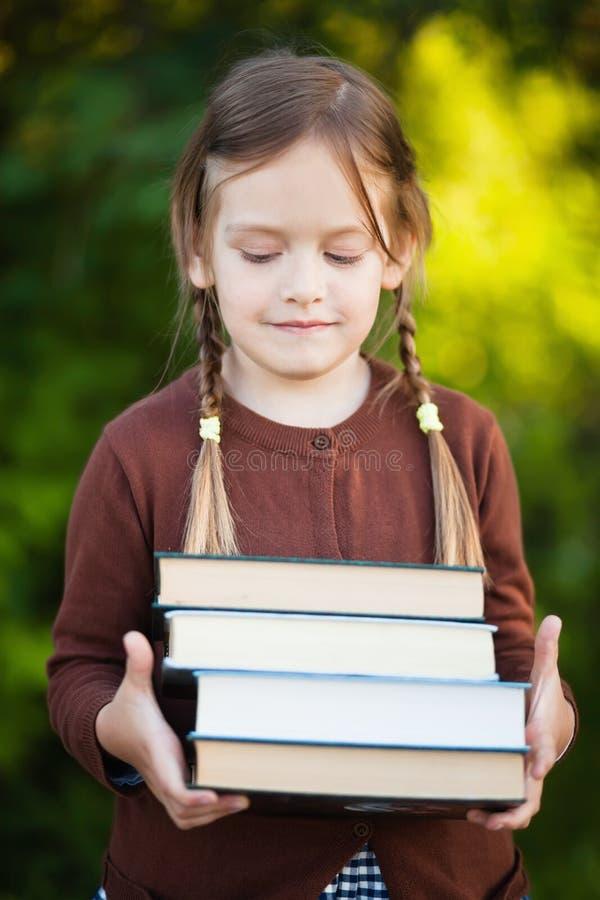 Preschool dziewczyny mienia stos książki i ono uśmiecha się zdjęcie stock