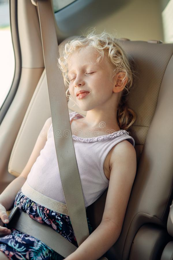 Preschool girl child sitting in car seat . Sleeping kid in automobile stock images
