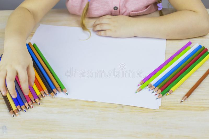 Young girl draws with colored pencils on paper. Preschool girl draws with colored pencils on paper royalty free stock photo