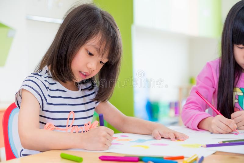 Preschool girl kid drawing with color pencil on white paper on t royalty free stock photos