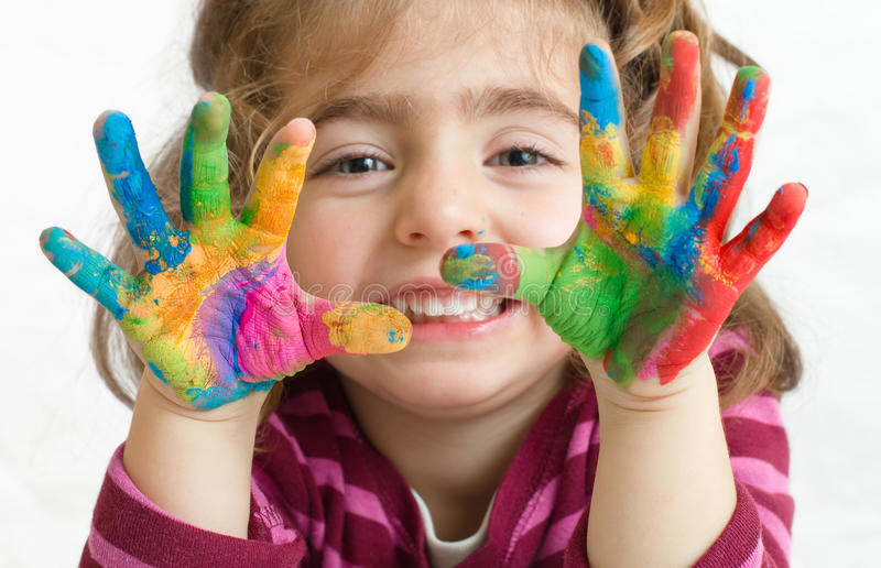 Preschool girl with painted hands. Portrait of a beautiful preschool girl with painted hands in background white stock photography