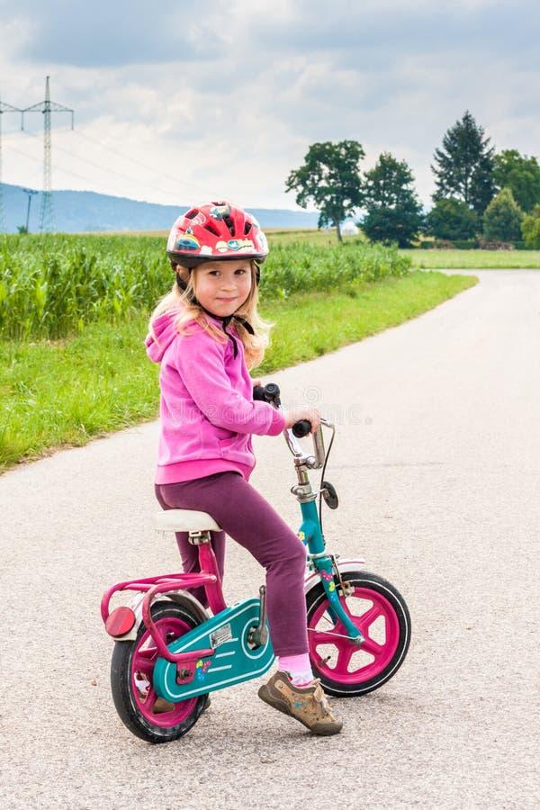 Preschool girl is sitting on bike stock photos