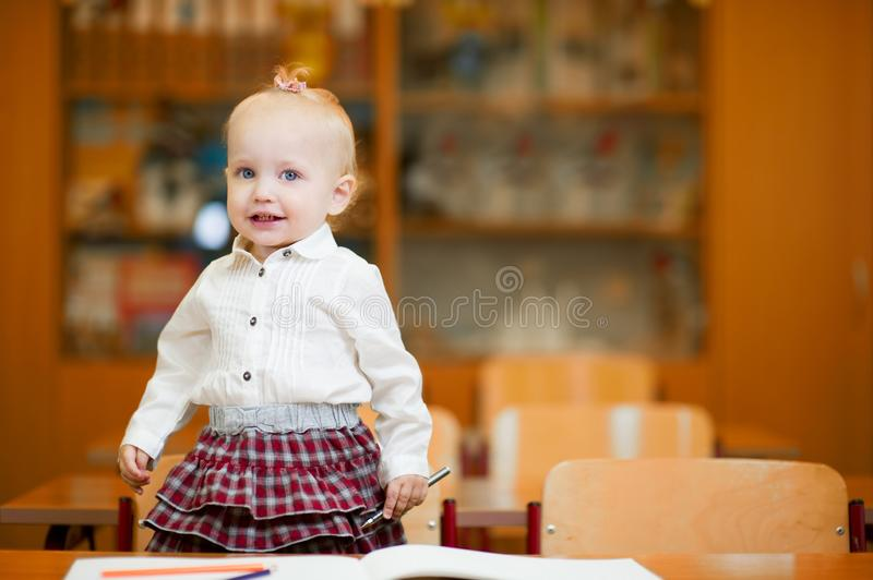 Preschool girl stands on a chair at a school desk. Little preschool girl stands on a chair at a school desk royalty free stock photography