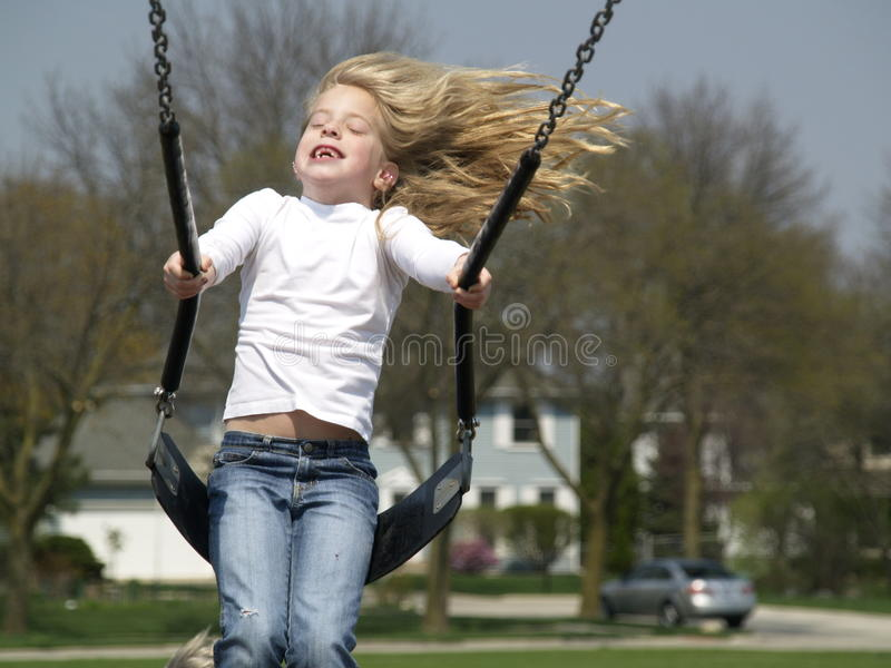Preschool girl on swing stock photo