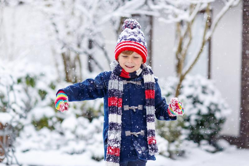 Cute little funny child in colorful winter fashion clothes having fun and playing with snow, outdoors during snowfall. Preschool kid boy in colorful clothes stock photo