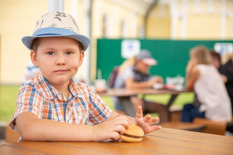 Preschool kid boy eats hamburger sitting in nursery cafe,Cute happy boy eating hamburger sitting in the restaurant royalty free stock images