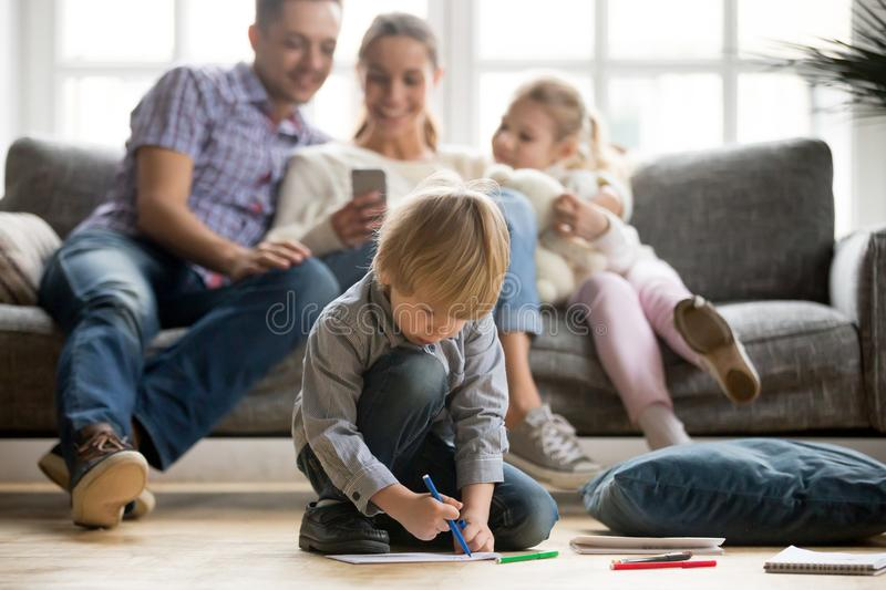 Preschool kid boy holding color marker drawing playing at home. Serious cute son holding color marker drawing on floor while parents with sister sitting apart royalty free stock image