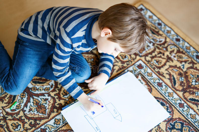 Preschool kid boy at home making homework, painting a story with colorful pens. Cute little preschool kid boy at home making homework, painting a story with royalty free stock image