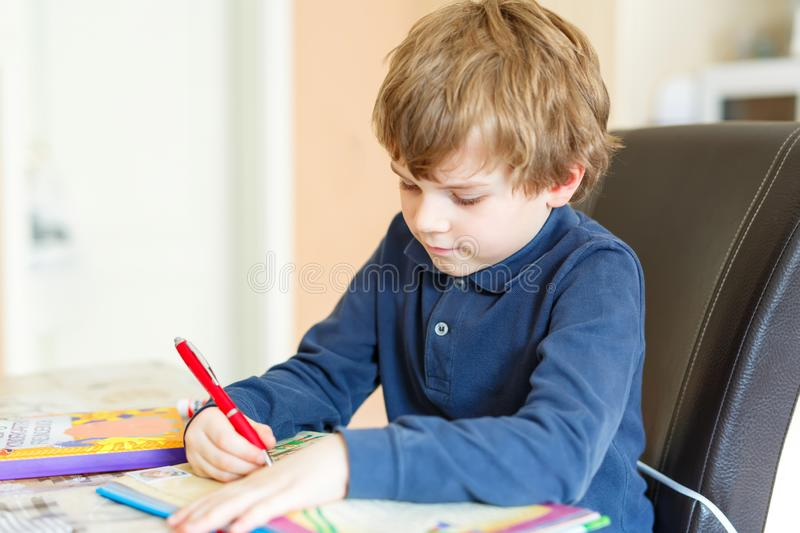 Preschool kid boy at home making homework writing letters with colorful pens. Cute little preschool kid boy at home making homework, writing letters with royalty free stock image