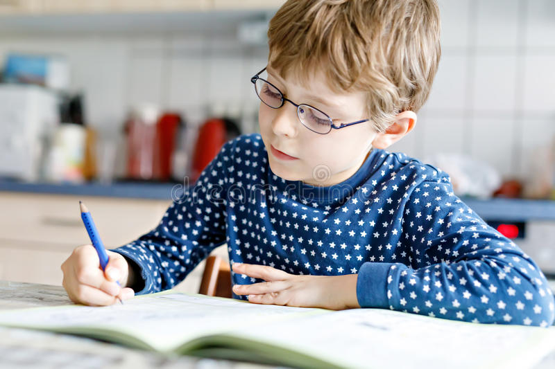 Preschool kid boy at home making homework writing letters with colorful pens. Cute little kid boy with glasses at home making homework, writing letters with stock image