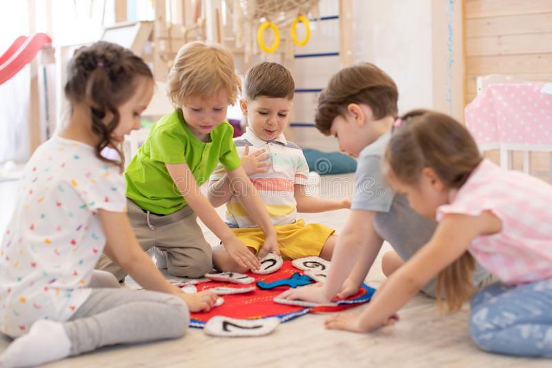 Preschool kids learning how to tell time from clock and set the hands in the correct position. Real people, moments. Children sit rounds on floor in kindergarten royalty free stock photography