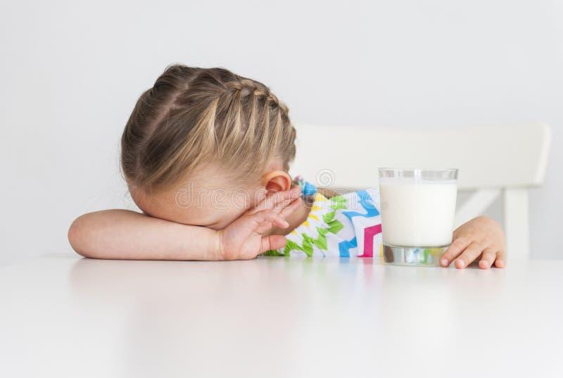 Preschool małej dziewczynki doesn ` t chce pić mleko, odosobniony, biały tło, obraz royalty free