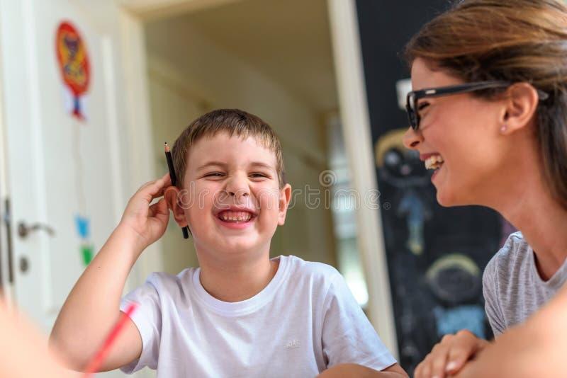 Preschool nauczyciel patrzeje mądrze dziecka przy dziecinem obraz royalty free