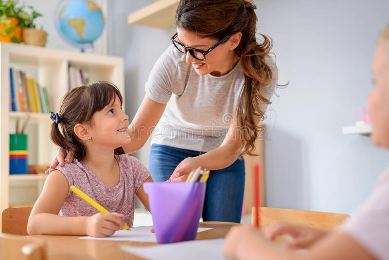 Preschool nauczyciel patrzeje mądrze dziecko uczenie pisać i rysować zdjęcia royalty free