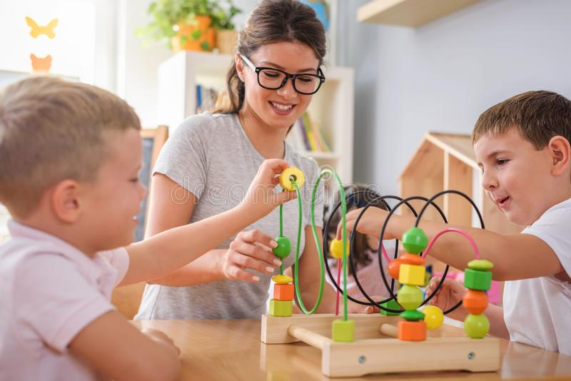 Preschool nauczyciel z dziećmi bawić się z kolorowymi dydaktycznymi zabawkami przy dziecinem obraz royalty free
