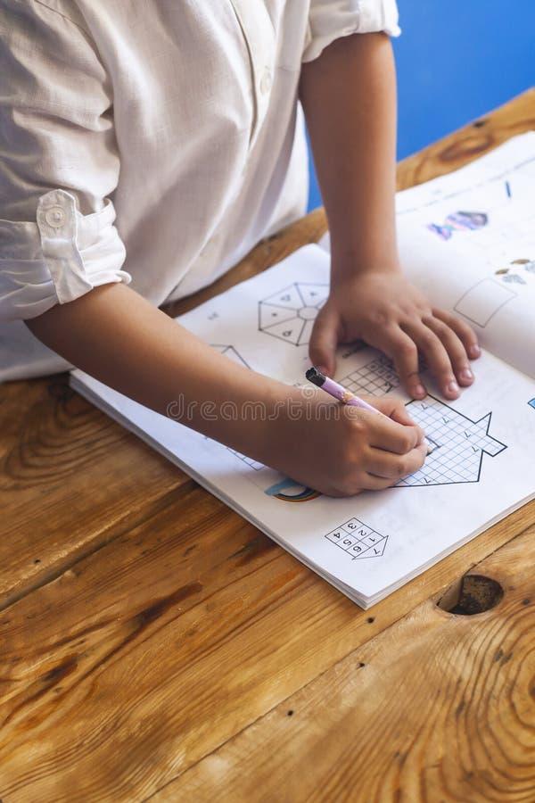 Preschool pełnoletni dziecko robi matematyce ch?opak robi troch? pracy domowej Rysować na dzieciaka notepad wolna przestrze? zdjęcia royalty free