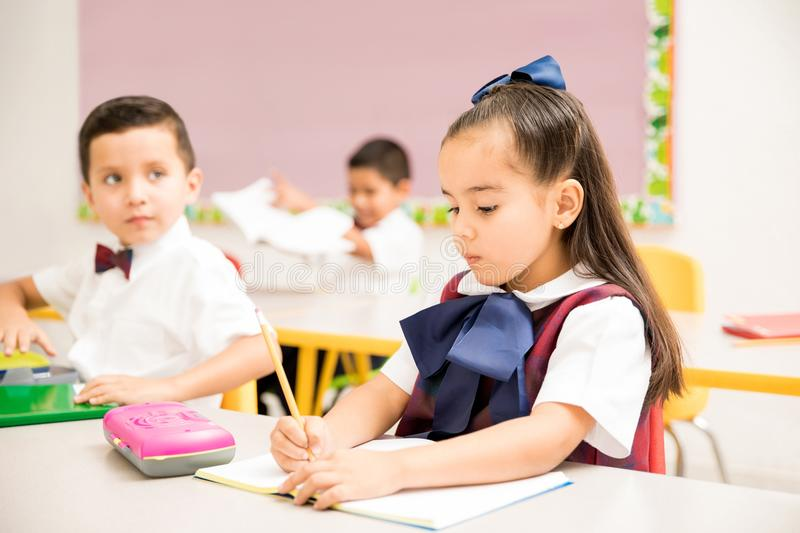 Preschool pupils writing in a classroom royalty free stock image