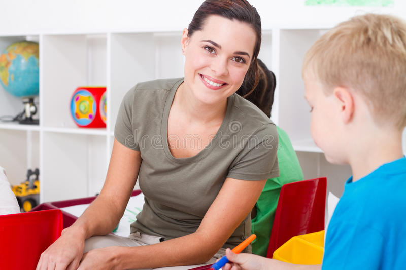 Preschool teacher. A happy preschool teacher smiling in classroom with her students royalty free stock images