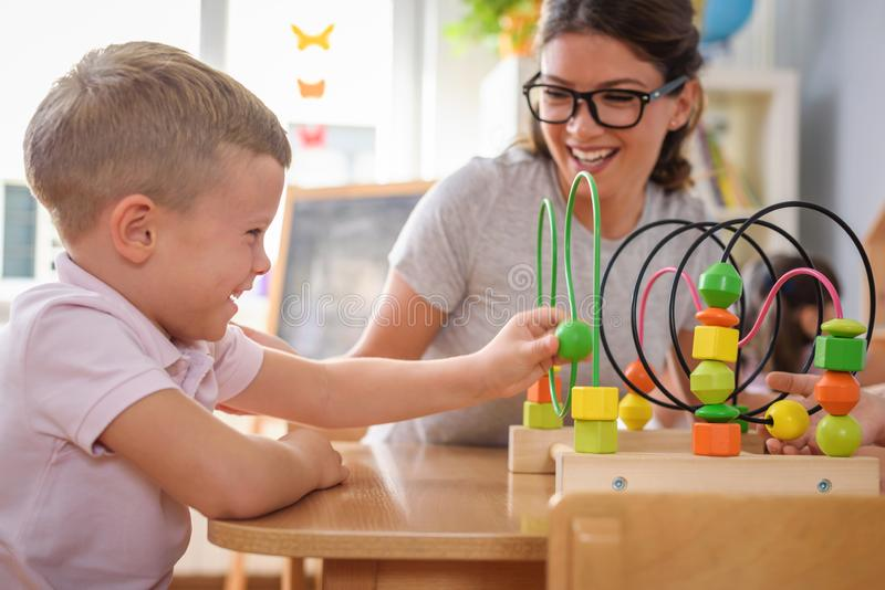 Preschool teacher with children playing with colorful didactic toys at kindergarten royalty free stock photography