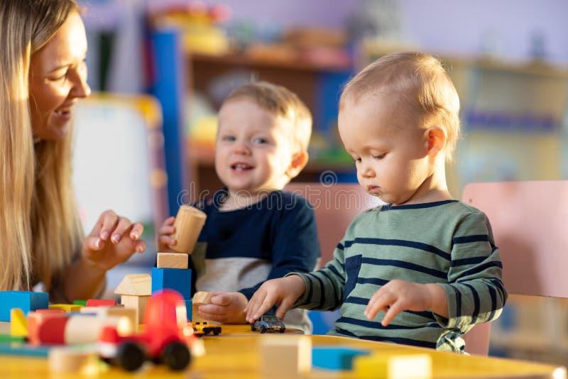 Preschool teacher and cute boys having fun time playing stock photo