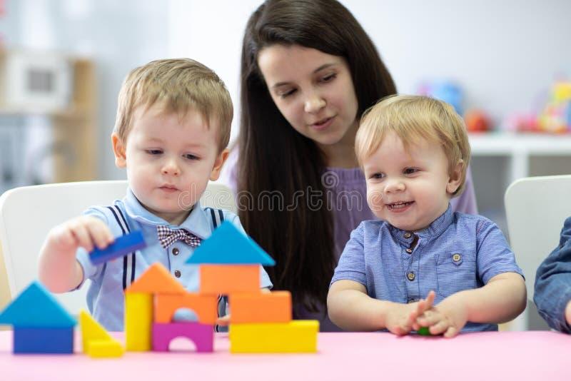 Preschool teacher and cute kids play in kindergarten stock photography