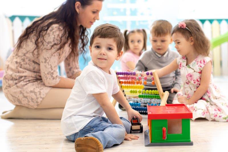 Preschool teacher and children in kindergarten stock photography