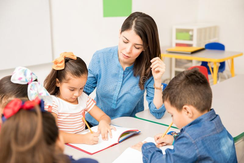 Preschool teacher helping her pupils royalty free stock photography
