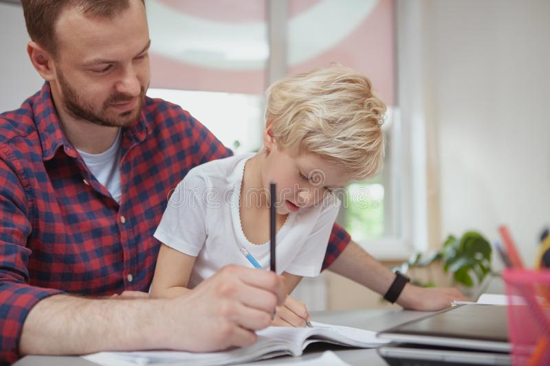 Friendly male teacher helping his little student. Preschool teacher helping his little student drawing, copy space. Adorable little girl enjoying drawing at stock photo