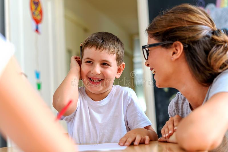 Preschool teacher looking at smart smiling boy at kindergarten royalty free stock images