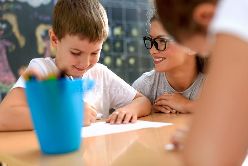 Preschool teacher looking at smart smiling boy at kindergarten. Preschool teacher looking at smart smiling boy that learning to write and draw. Early education stock images