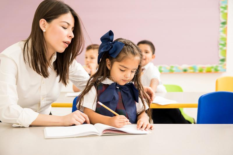 Teacher helping a student with an assigment. Preschool teacher sitting next to one of her students and helping her with her writing assignment stock photo