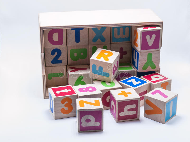Preschool Toys. Wooden cubes with colorful letters in a wooden box and a white background royalty free stock image