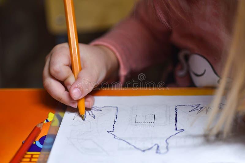 Preschooler ребенка учит нарисовать и написать в тетрадях дома в вечере под светом от лампы стола стоковая фотография
