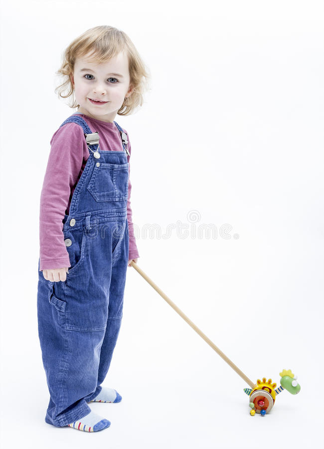 Preschooler με το παιχνίδι που στέκεται στο ελαφρύ υπόβαθρο στοκ φωτογραφίες