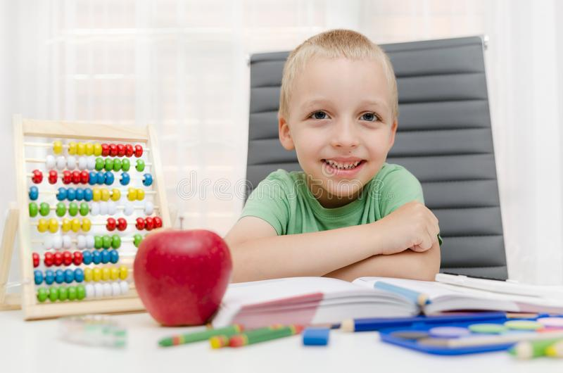 Preschooler, σπουδαστής που κάνει την εργασία στο γραφείο στο σπίτι στοκ εικόνα