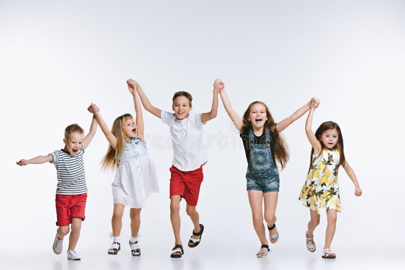 Preschooler моды группы милый ягнится друзья представляя совместно и смотря предпосылку камеры белую стоковое фото rf