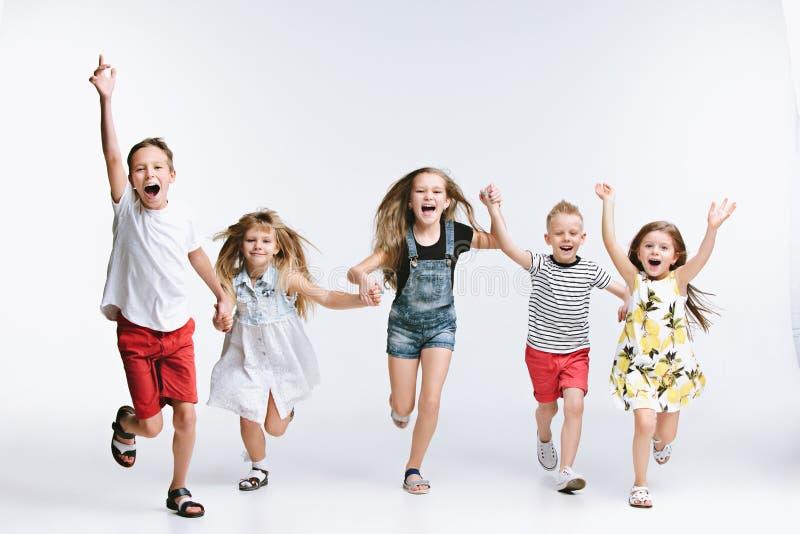 Preschooler моды группы милый ягнится друзья представляя совместно и смотря предпосылку камеры белую стоковая фотография