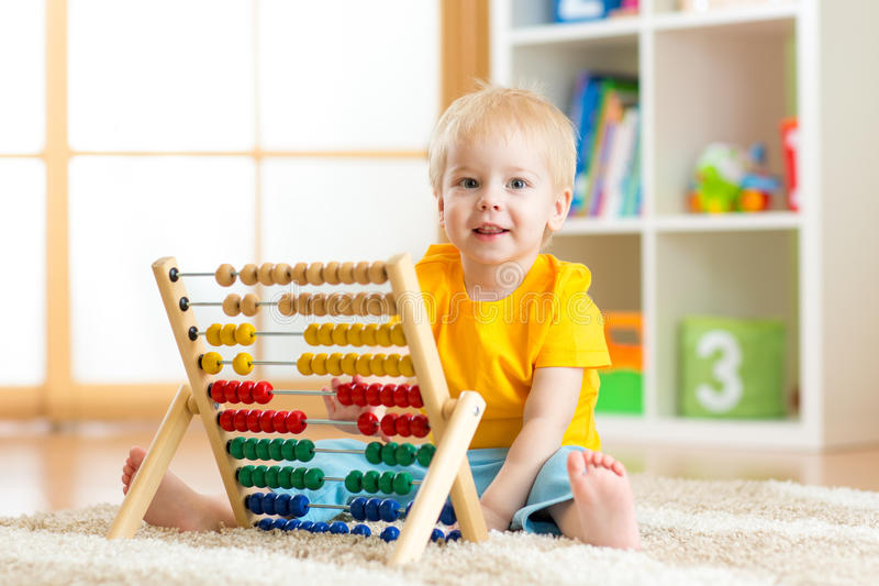 Preschooler baby learns to count. Cute child playing with abacus toy. Little boy having fun indoors at kindergarten royalty free stock photos