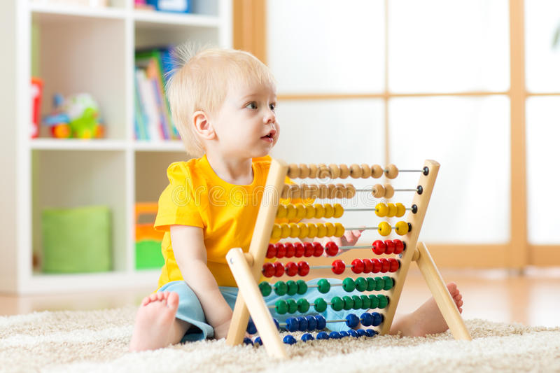 Preschooler baby learns to count. Cute child playing with abacus toy. Little boy having fun indoors at kindergarten royalty free stock photography