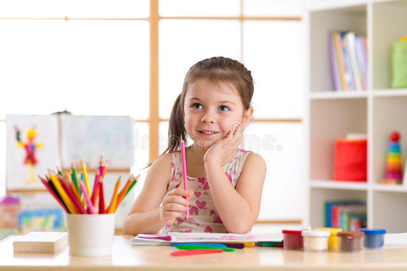 Preschooler child drawing and coloring by pencils royalty free stock photos