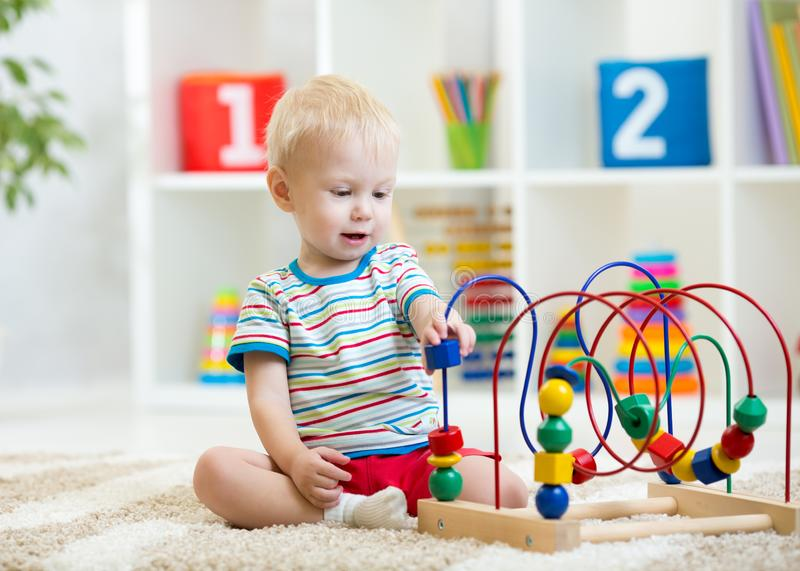 Preschooler child playing with developmental toy. Kid plays with toy beads at kindergarten or daycare center. Toddler. Preschooler child boy playing with royalty free stock images