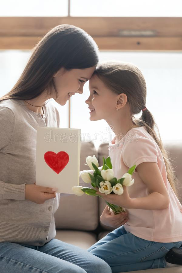 Preschooler child present flowers and postcard to young mom royalty free stock image