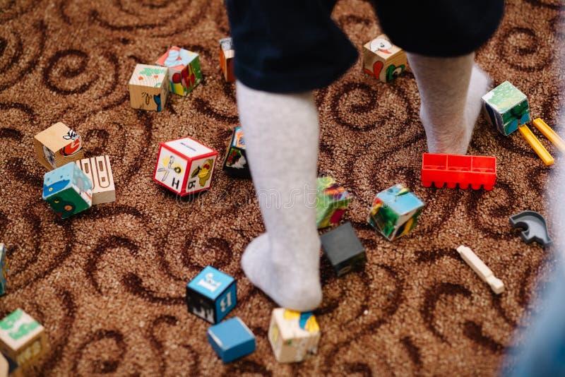Preschooler dzieciak bawi? si? z kolorowymi drewnianymi blokami Edukacyjne zabawki w dziecinu rozpraszali na pod?odze obraz stock