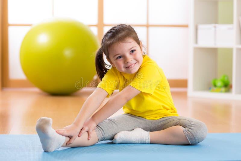 Preschooler dziecka dziewczyna robi sprawności fizycznych ćwiczeniom fotografia stock