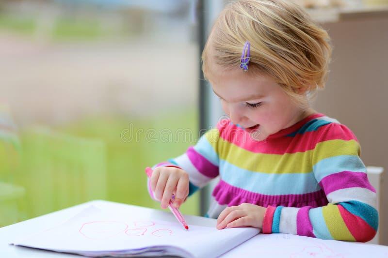 Preschooler dziewczyny rysunek na papierze z porady piórem fotografia royalty free