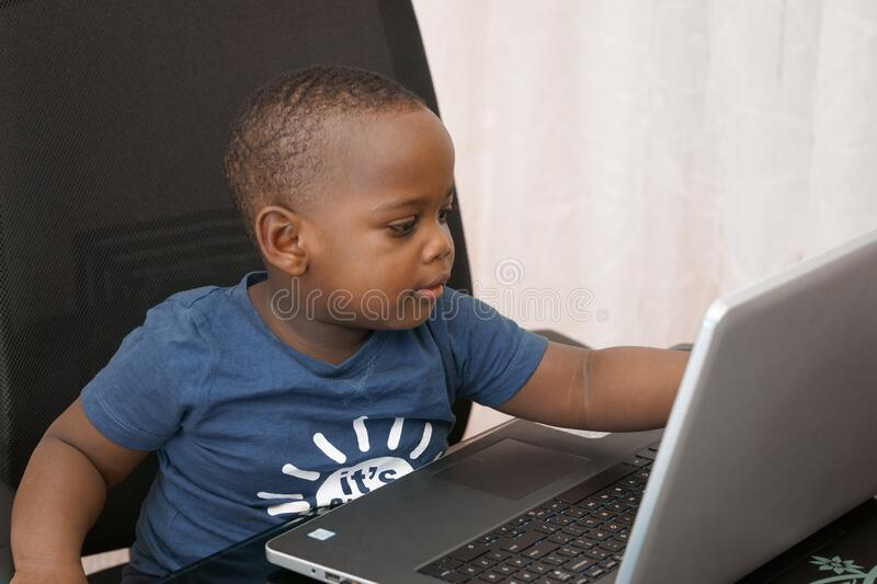 Preschooler e-learning online at home with a laptop stock photo