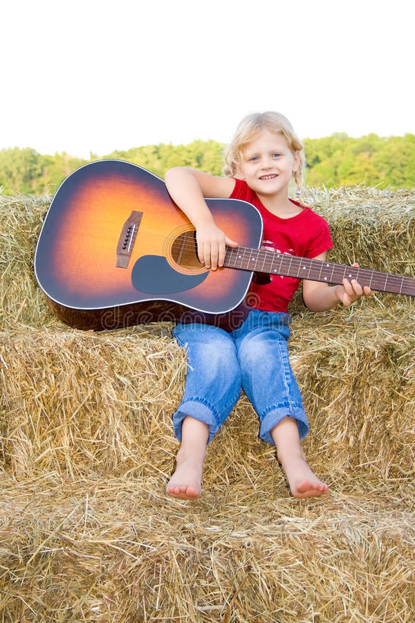 Preschooler felice che gioca la chitarra. fotografia stock